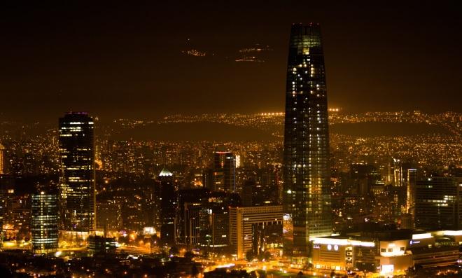 Vista noturna de Santiago com Cordilheira dos Andes ao fundo.